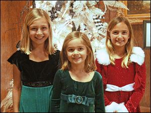 Sisters Kate, 10, left, Lindsey, 5, center, and Sara Stapleton, 8, loved viewing all the Christmas trees on display at the Toledo Club.