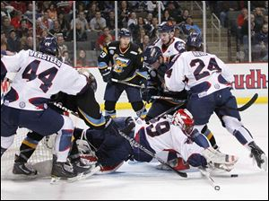 Kalamazoo goalie Joel Martin (49) dives on the puck in a crowd against the Walleye during the first period.