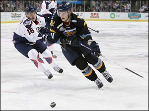 Walleye player Andrej Nestrasil (11) takes the puck past Kalamazoo Wings' Joe Charlebois (16) during the first period.