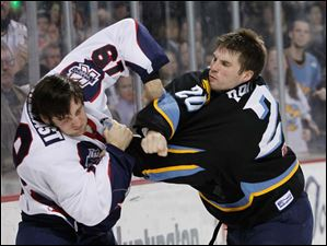 Toledo's Phil Rauch (20) lands a right cross on  Wings player Tyler Shelast (19) during a fight in the second period.