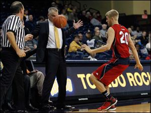 Toledo coach Tod Kowalczyk is face to face with the ball as UIC's Anthony Kelley chases it during second half.