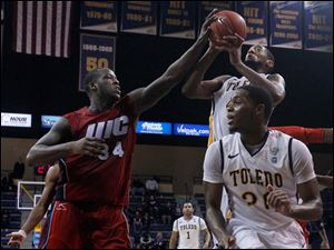 The Flames' Josh Crittle blocks the shot of Toledo's Matt Smith as UT's Julius Brown ducks down.