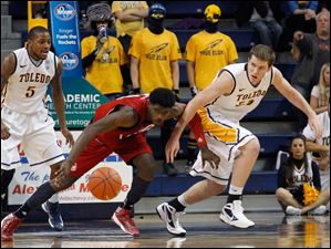Rian Pearson, left, watches as UIC's Marc Brown and Toledo teammate Richard Wonnell chase a loose ball during.