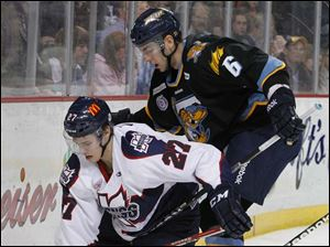 Toledo's Max Nicastro (6) battles Kalamazoo Wings player Alexandre Mallet (27) for the puck.
