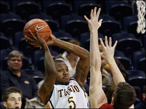 Toledo's Rian Pearson passes the ball through hands of UIC's Will Simonton.
