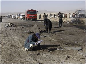 Pakistani police officers, collect evidence from the site of a suicide bombing in Quetta, Pakistan, Sunday.