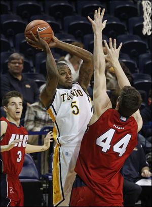 UT's Rian Pearson, who scored 24 points and grabbed 10 rebounds, passes against Illinois-Chicago's Will Simonton in Saturday's game at Savage Arena. The Rockets improved their record to 4-6.