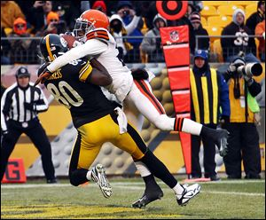 Steelers receiver Plaxico Burress makes a touchdown catch despite pressure from the Browns' Joe Haden. The Steelers finish the year at 8-8, while the Browns dropped three straight to finish 5-11.