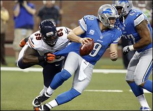 Detroit Lions quarterback Matthew Stafford pulls away from the Bears' Henry Melton, but he wasn't able to escape another loss. He fumbled and threw a costly interception.