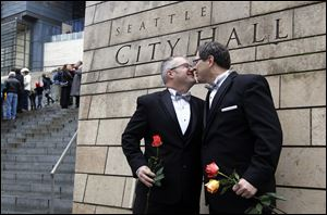 Terry Gilbert, left, celebrates with his husband Paul Beppler after their wedding at Seattle City Hall, becoming among the first gay couples to legally wed in the state of Washington.