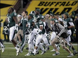 Michigan State players celebrate on the field after winning the Buffalo Wild Wings Bowl against TCU on Saturday in Tempe, Ariz.