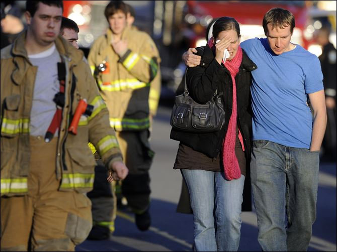 Robert and Alissa Parker leave a firehouse staging area after the shooting at Sandy Hook Elementary in Newtown, Conn., where a gunman killed 26 children and adults, including the Parkers' daughter Emilie, 6.