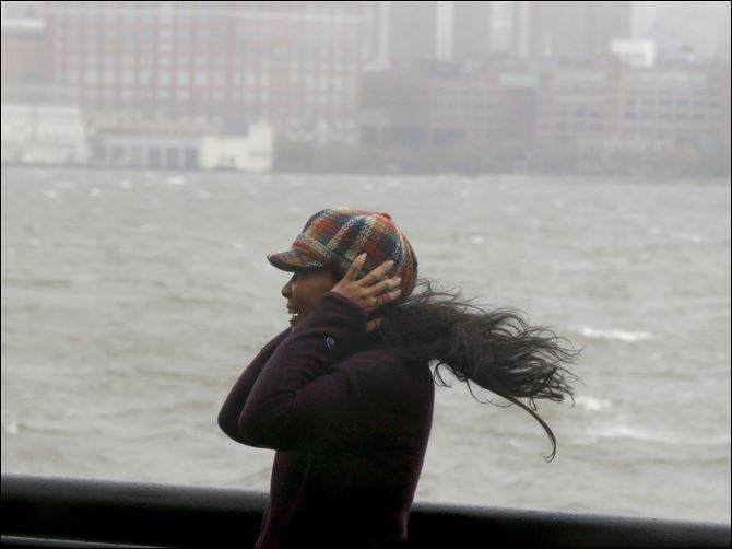 A woman covers her ears in Hoboken, N.J., as Hurricane Sandy bears down on the New York City area.