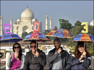 Tourists pose as they carry umbrellas with numbers to welcome the New Year 2013 on the terrace of a hotel in the backdrop of Taj Mahal in Agra, India.