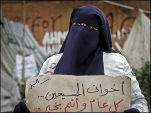 "An Egyptian woman holds a poster with Arabic that reads, ""my Christian siblings ... happy new year..."" in front of the presidential palace in Cairo, Egypt."