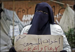 An Egyptian woman holds a poster with Arabic that reads,