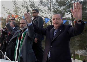 Turkish Prime Minister Recep Tayyip Erdogan, right, flanked by the Syrian opposition coalition leader Mouaz al-Khatib, waves to people as he addresses residents of a Turkish village near the Syrian border in Sanliurfa, Turkey on Sunday.