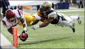 Southern California running back Silas Redd, left, dives into the end zone past Georgia Tech's Louis Young during the Sun Bowl today in El Paso, Texas.