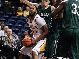 Toledo's Reese Holliday is surrounded by Chicago State defenders as he looks to the basket.