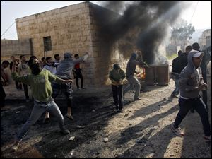 Palestinians hurl stones at Israeli soldiers, not seen, during clashes in the West Bank village of Tamoun, near Jenin.