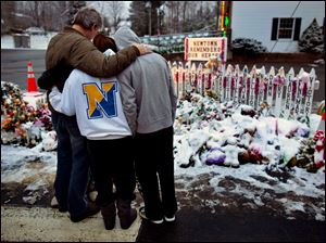 Members of the Rutter family of Sandy Hook, Conn., embrace early Christmas morning as they stand near memorials by the Sandy Hook firehouse in Newtown, Conn. People continue to visit memorials after gunman Adam Lanza walked into Sandy Hook Elementary School in Newtown, Conn., Dec. 14, and opened fire, killing 26, including 20 children, before killing himself.