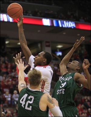 Ohio State's Deshaun Thomas, center, shoots between Chicago State's Matt Ross, left, and Quincy Ukaigwe during the second half of Saturday's game. Ohio State defeated Chicago State 87-44.