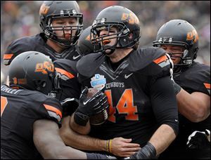 Oklahoma State tight end Jeremy Seaton (44) celebrates with teammates after a first-half touchdown against Purdue during the Heart of Dallas Bowl. Oklahoma State beat Purdue 58-14.