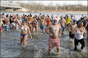 Swimmers hit the cold water of the Maumee River during the 84th annual New Year's Day polar bear plunge in Waterville, Ohio.