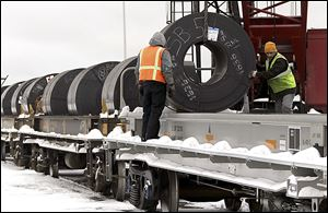 Steel coils are loaded onto rail cars at the Port of Cleveland. About 160 rail cars — which can carry more cargo and take it farther than trucks can — will be loaded with three shiploads of steel in the coming weeks.