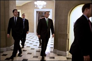 Speaker of the House John Boehner, R-Ohio, center, returns to his office from the House chamber in the evening at the Capitol in Washington as talks continue regarding the