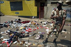 An Ivory Coast troop stands next to the belongings of people involved in a deadly stampede in Abidjan, Ivory Coast, today.