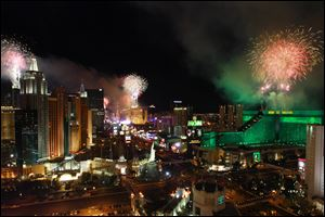 Fireworks explode from the tops of casinos on the Strip during the annual New Year's Eve celebration in Las Vegas.