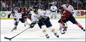 Walleye defenseman Cody Lampl, center, prides himself on being able to move the puck to the team's forwards quickly as he maneuvers up the ice recently against Kalamazoo at the Huntington Center.