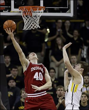 Indiana forward Cody Zeller, left, shoots in front of Iowa center Adam Woodbury. Zeller leads the top scoring offense in the nation.