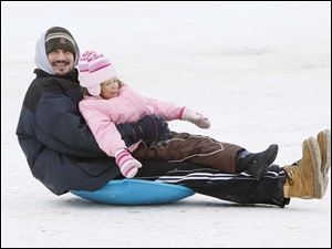 Jeff Shepler, Temperance, hangs on tight to his daughter Phoebe Shepler, 4, as they zoom down the sledding hill at Sidecut Metropark Preserve.  The pair, along with Jeff's other daughter and Phoebe's sister Alison Shepler, were enjoying the holiday break.