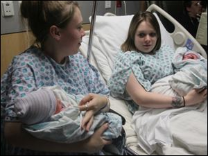 Twin sisters Aimee Nelson, left, and Ashlee Nelson, both of Cuyahoga Falls, hold their newborn sons Donavyn Bratten, left, and Aiden Lee Alan Dilts at Summa City Hospital on Monday in Akron.
