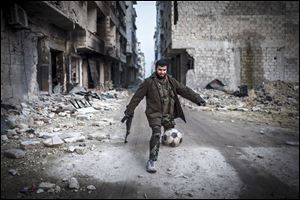 A Syrian rebel plays football today in the Saif al-Dawlah neighborhood of Aleppo, Syria,