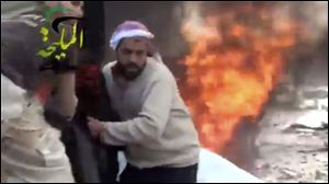 This citizen journalism image taken from video provided by Shaam News Network, shows a wounded man being pulled from the site of a Syrian government airstrike on a gas station in the eastern Damascus suburb of Mleiha, Syria.
