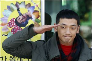 South Korean pop singer Rain gives a military salute to his fans before he enters the army to serve in October, 2011.
