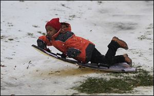 Brandon Sims, 9, hits a ramp sledding down one of the hills in Ottawa Park in Toledo.