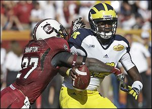Michigan quarterback Devin Gardner (12) is sacked by South Carolina cornerback Victor Hampton (27) during the second quarter of the Outback Bowl on Tuesday.
