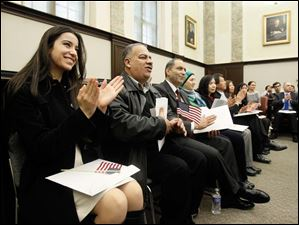 New U.S. citizens Rima Adel Abu-Hamdan, left, from Lebanon, Osama Jawdat Al Souqui, center, from Jordan, and Ragheb Akram Assaly, right, applaud..
