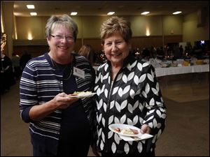 Judy Gajdostik, of Shrader Tire and Oil, and Gerri Kruszynski, a retiree of Shrader, pose for a picture at the Beach House Christmas by Candlelight in Toledo.
