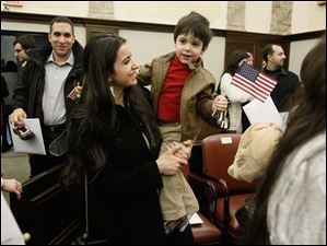 New U.S. citizen Rima Adel Abu-Hamdan, from Lebanon, holds her son Adam Abu-Hamdan ,2, today while her husband Maher Abu-Hamdan, back, follows.