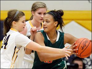 Central Catholic's Demi Russell (40) looks for an opening as she is defended by Whitmer's Mackenzie Tracy (34) and Samantha Meinen.