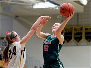 Central Catholic's Michelle Murnen goes to the net as she is guarded by Whitmer's Tricia Kimmel.