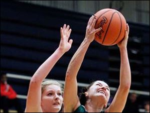 Central Catholic's Jen Vliet (14) battles Whitmer's Samantha Meinen (12) for a loose ball.