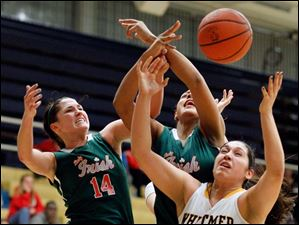 Central Catholic's Jen Vliet (14) and Demi Russell (40) battle Whitmer's Abigial Sarabia (40) for a rebound.