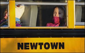 A girl sits on a Newtown bus leaving the new Sandy Hook Elementary School after the first day of classes today in Monroe, Conn.