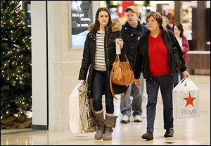 Jen Hutson, left, and her mother, Nancy Hutson, search for deals at Westfield Franklin Park mall. Promotions in the waning days before Christmas helped boost the entire holiday shopping season.